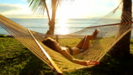 Beautiful Young Woman Relaxing in Tropical Hammock at Sunset. video
