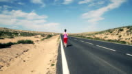 Beautiful young woman running on the road video