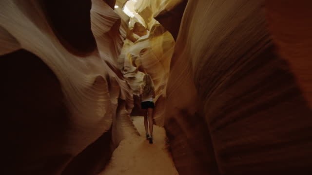 A beautiful young woman runs, exercising, through unique caves video