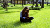 beautiful young woman sitting in the park on the grass and reading a book video