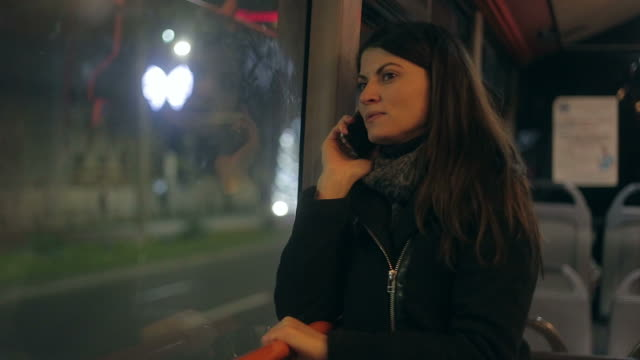 Beautiful young woman speaking at mobile phone in the bus. video