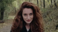 Beautiful young woman standing and smiling in forest video