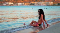 beautiful young woman standing by the sea relaxing in the Malta sunset video