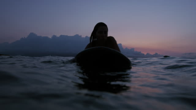 Beautiful young woman surfing in bikini at sunset in slow motion video