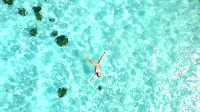 AERIAL SLOW MOTION: Beautiful young woman swimming, lying on a water surface in crystal clear ocean video