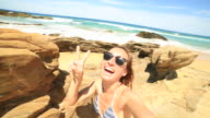 Beautiful young woman takes a selfie portrait on the beach video