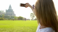 Beautiful young woman taking picture in Ottawa using mobile phone video