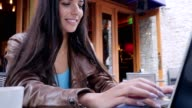 Beautiful young woman uses laptop at outdoor cafe video