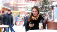 Beautiful young woman using a smartphone and drinking hot tea during the Christmas Fair video