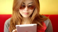 Beautiful young woman using digital tablet video