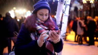 Beautiful young woman using her mobile phone at night. video