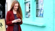 Beautiful young woman using her smartphone, walking.. video