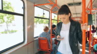Beautiful young woman using mobile phone on tram/train. video