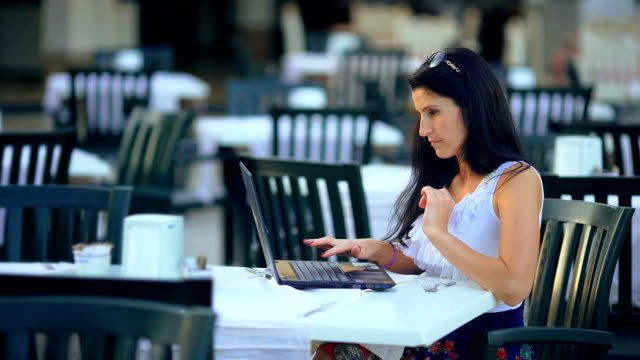Beautiful young woman with a laptop working in modern cafe. video