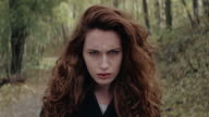 Beautiful young woman with grumpy face standing in forest video
