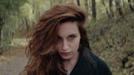 Beautiful young woman with solemn face standing in forest video