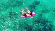 Beautiful Young Women In Bikinis Floating on Pink Inflatable Raft in Crystal Ocean in Hawaii. video