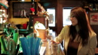 beautifull woman drinks beer in a pub - dolly video