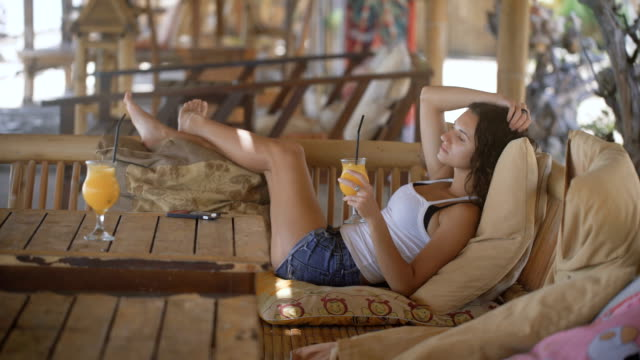 Beautifully girl lying on a lounger on a resort in Bali. Young woman drink cocktail through a straw while relaxing in the hotel. Brunette stir the liquid in the glass and looks into the distance video