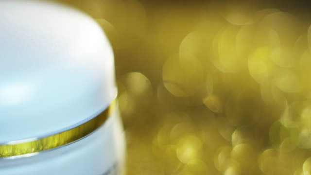 Beauty cream golden high quality for sensitive skin and rejuvenation based on hyaluronic acid turns with particles of gold in the background. concept of beauty and wealth in beauty creams for the skin video