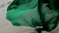 Beauty Girl in green dress running on sand dune while wind blowing her clothes slow motion foot close up video