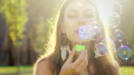 Beauty girl is blowing soap bubbles video