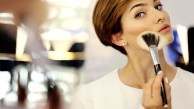 Beauty woman applying makeup. Beautiful girl looking in the mirror and applying cosmetic on the cheekbones with a big brush video