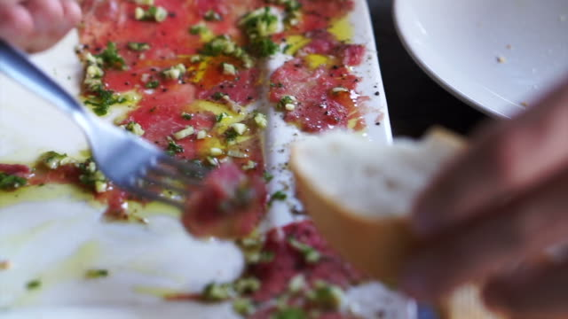 Beef carpaccio appetizer dish. hand putting sliced raw beef on bread video