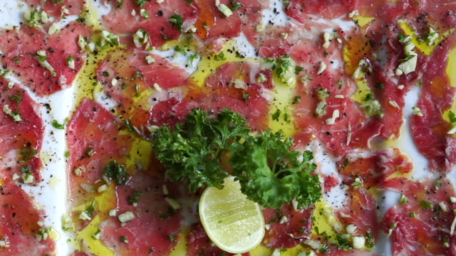 Beef carpaccio appetizer dish, sliced raw beef with olive oil, garlic and lime close up texture video
