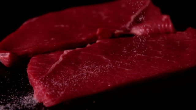 Beef steaks on black surface being seasoned video