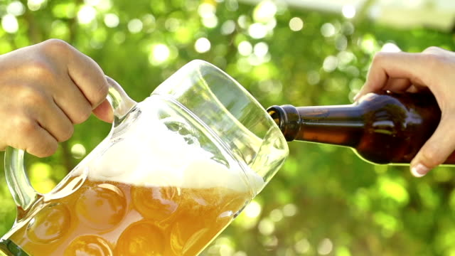 Beer being poured into glass in slow motion video