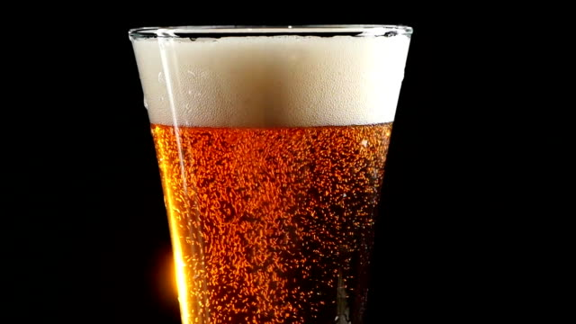 Beer is pouring into a glass on black background. Slow video