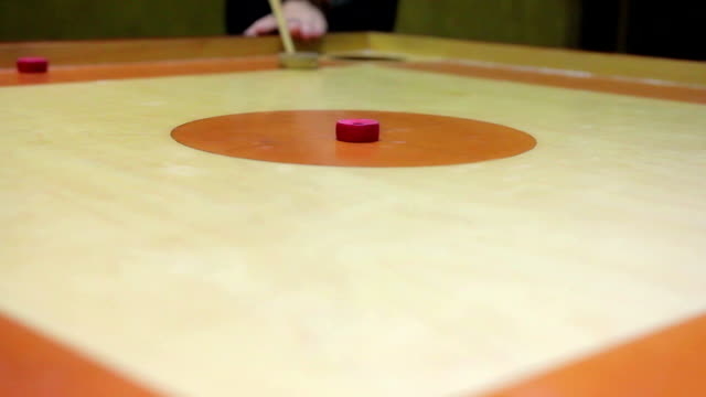 Beginner playing carrom game, friends having fun at leisure, indoor activity video