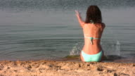 behind girl sit on beach in swim suit video