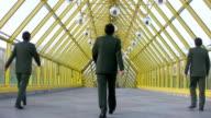 Behind marching businessmen clones on bridge video