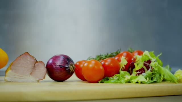 bell pepper, bacon, onions, tomatoes and lettuce, lying on a wooden stand video