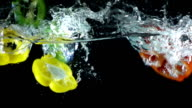 Bell peppers splashing into water, slow motion video
