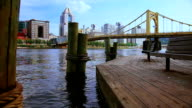 Benches on the wooden pier opposite Pittsburgh cityscape. video