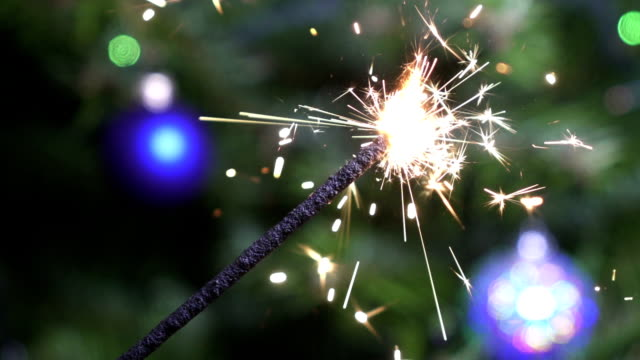 Bengal light against the background of a Christmas tree with New Year's balls,slow-motion video