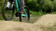 Bicycle BMX racer rides track in red shirt, spinning pedals video
