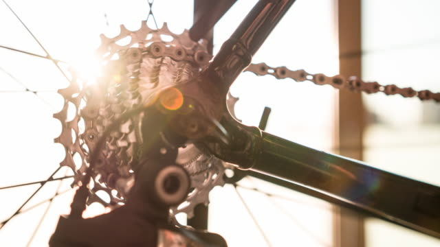 Bicycle gear and chain in motion at sunrise video
