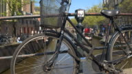DOF: Bicycle locked on old bridge with crowded riverbank and canal in background video