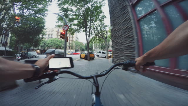 POV bicycle riding in the city, while consulting a map on mobile phone video
