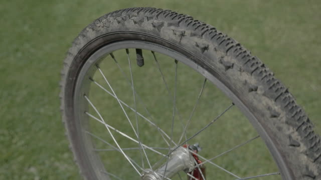 Bicycle wheel cover. Bicycle tire. Rotating spinning wheel with field sample. video
