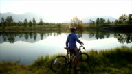 Bicyclist pauses in front of mountain lake at sunrise video