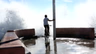 Bicyclist pedals to end of pier as surf crashes video