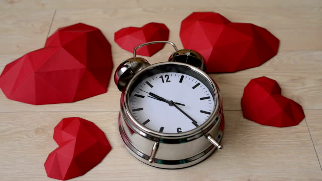 Big alarm clock with red polygonal paper heart shapes video