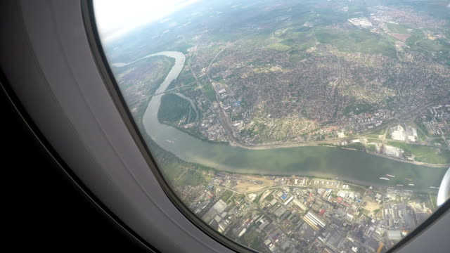 Big city on banks of wide river, nice view from air through airplane window video