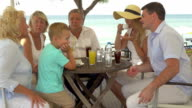 Big family sitting at table on the sea coast in city of Perea, Greece video