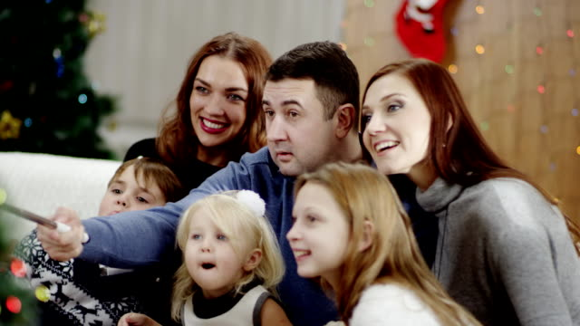 big family taking photo with selfie stick at christmas party video